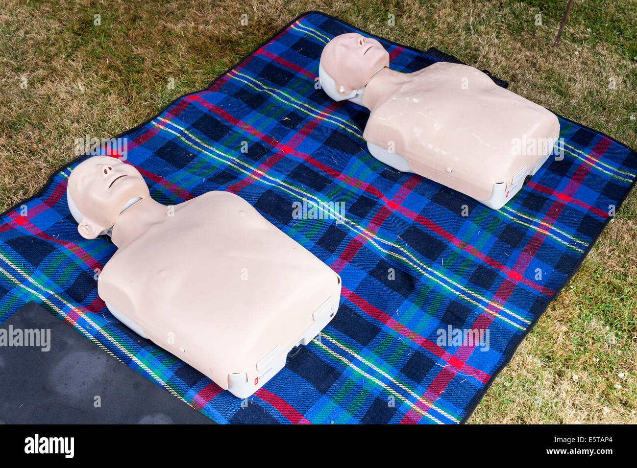 Resuscitation dummies or CPR manikins laid on a blanket for first aid training. - Stock Image