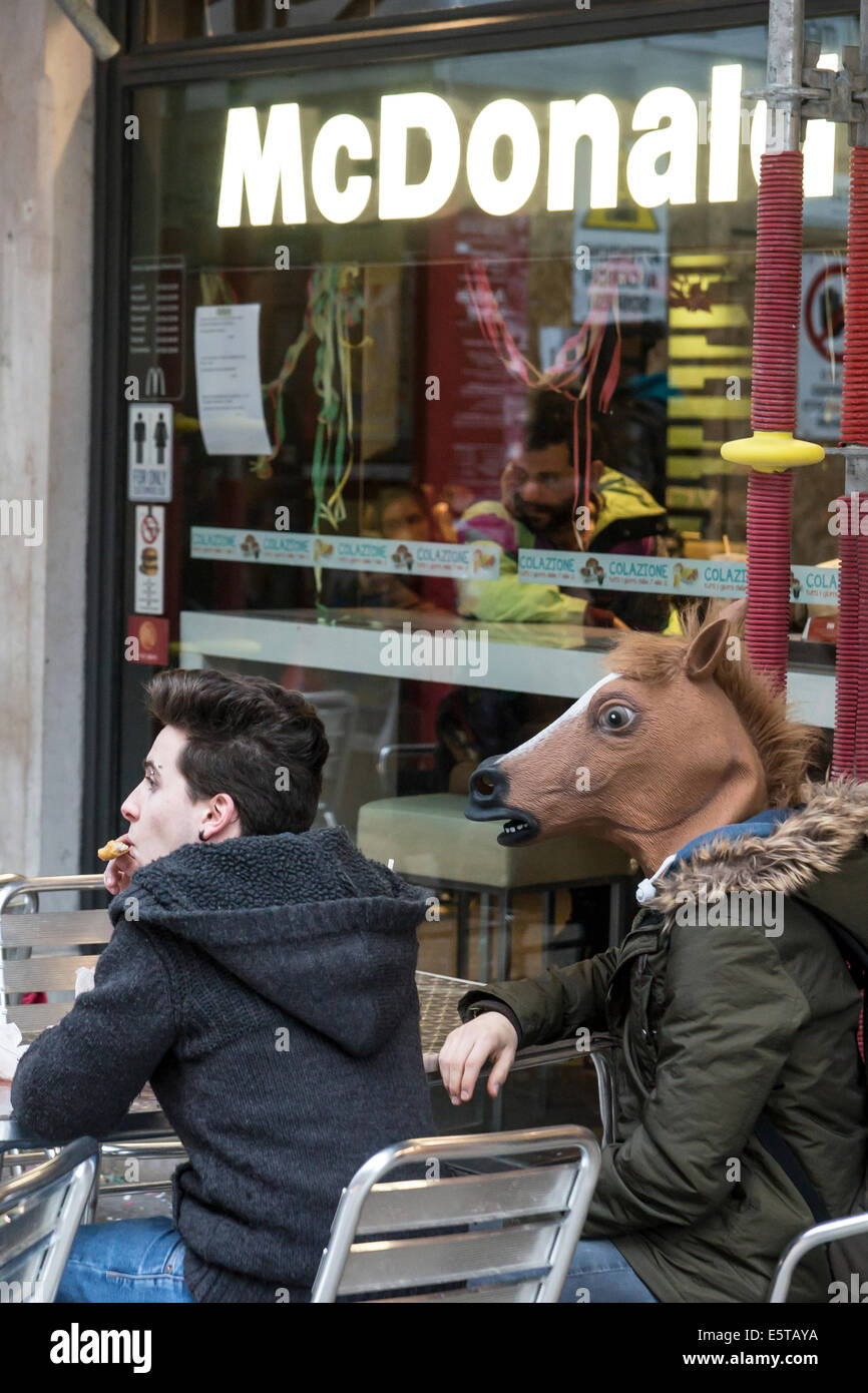 Horse head mask man and friend enjoy fast food even during Carnival in Venice. - Stock Image