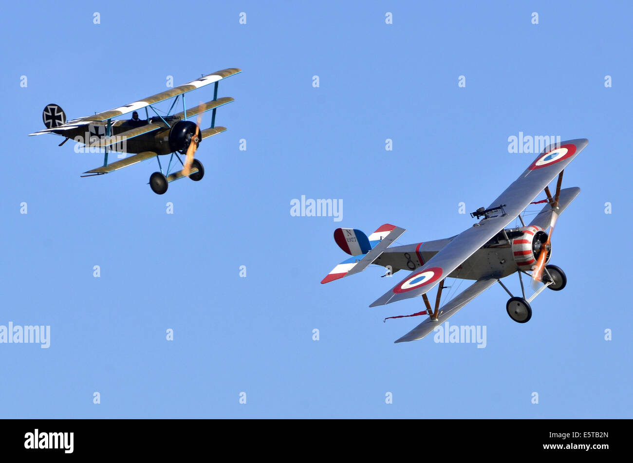 WW1 plane dogfight. Fokker Triplane DR-1 in German markings and Nieuport 23 Scout in French markings simulate a - Stock Image
