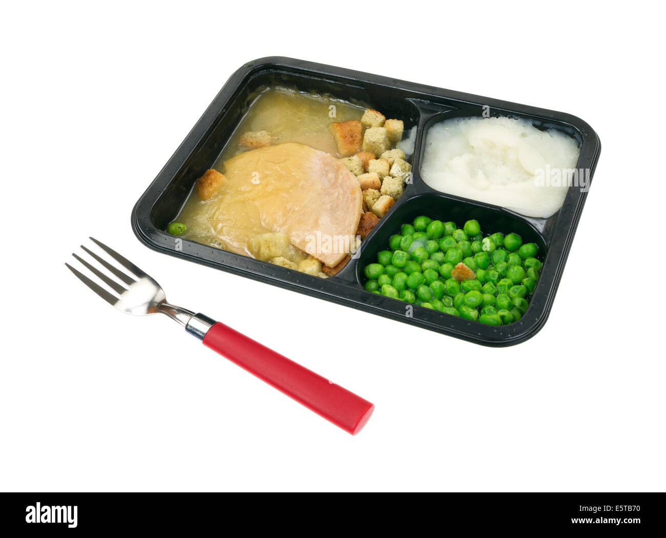 A sliced turkey in gravy with mashed potatoes and green peas TV dinner in black tray with red handled fork in the - Stock Image