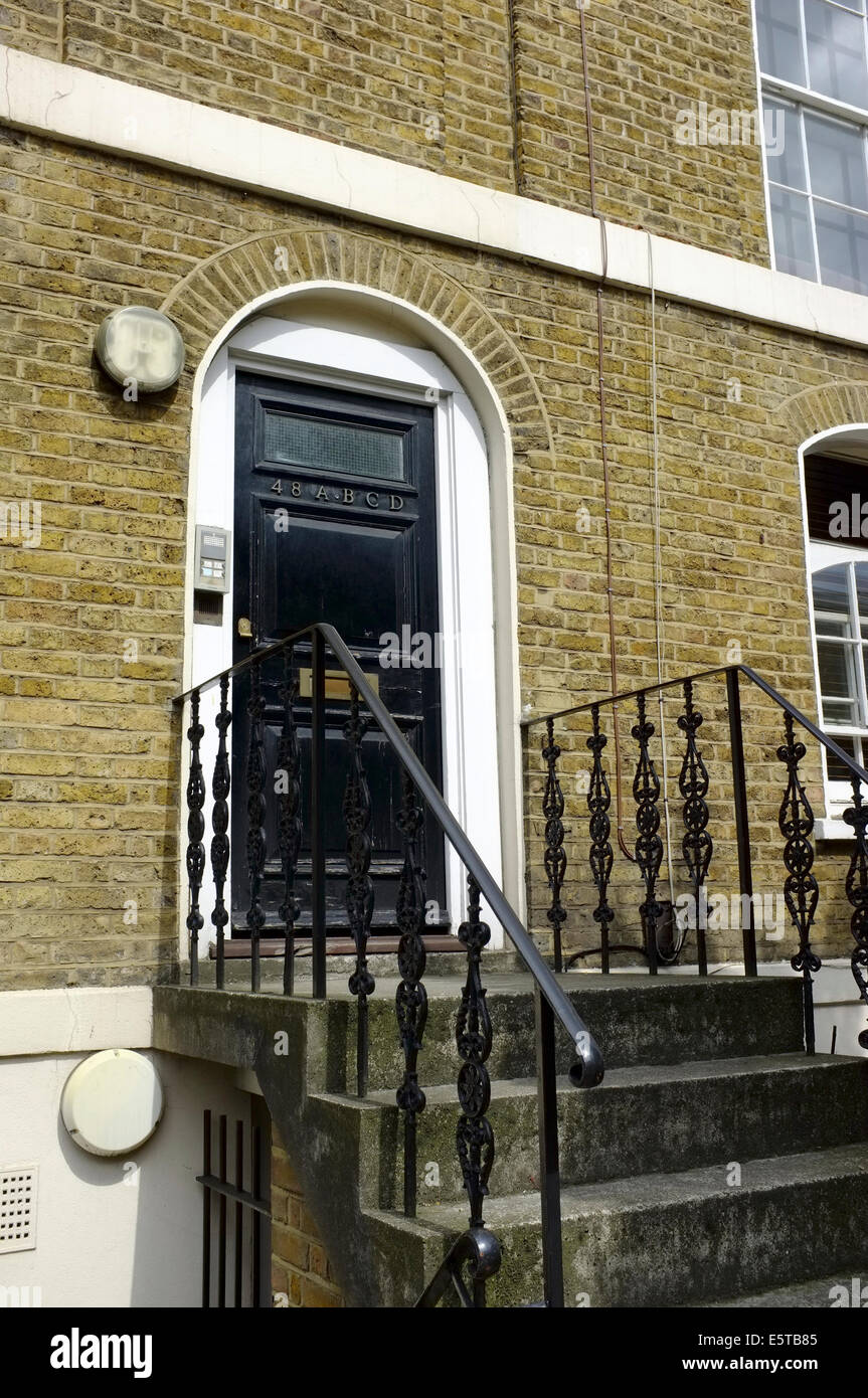 steps up to a door shared by 4 tenants in London - Stock Image