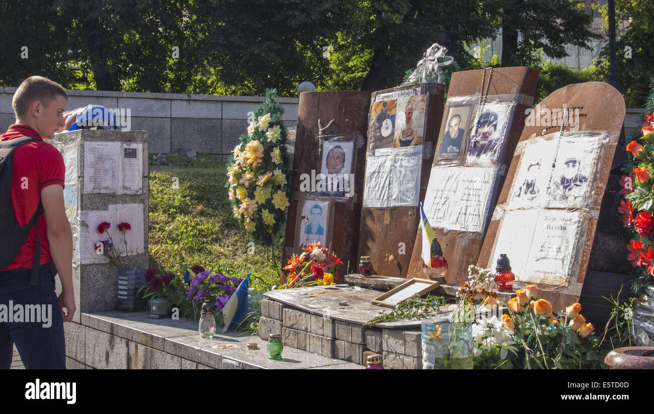 The young man examines portraits of those killed during the clashes in the Ukrainian capital. 5th Aug, 2014. -- - Stock Image