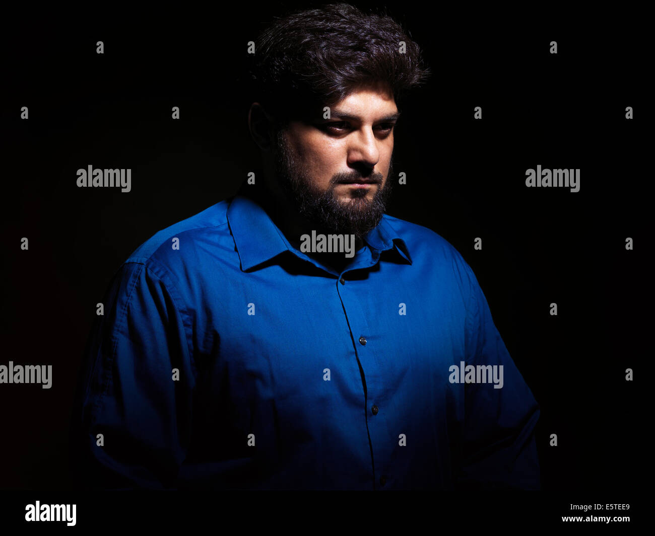 Portrait of a pakistani man isolated on black background - Stock Image