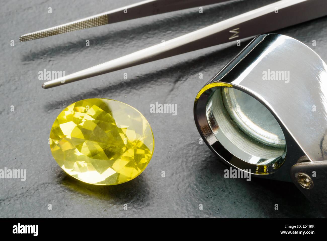 Yellow lemon quartz gemstone with tweezers and loupe on black stone plate. - Stock Image