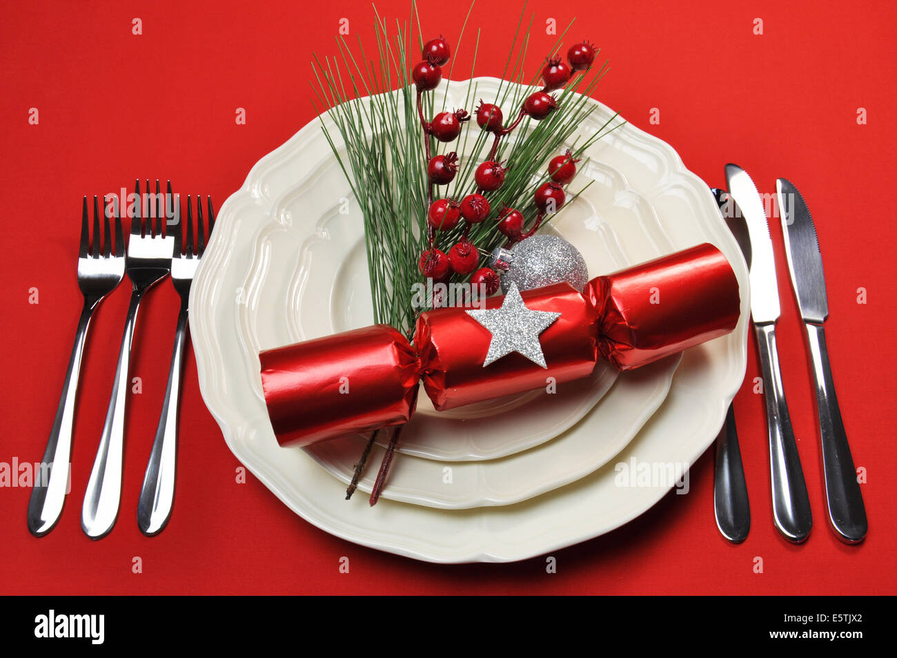 Modern bright red Christmas table setting with cracker and baubles plates and cutlery on a red tablecloth background. & Modern bright red Christmas table setting with cracker and baubles ...