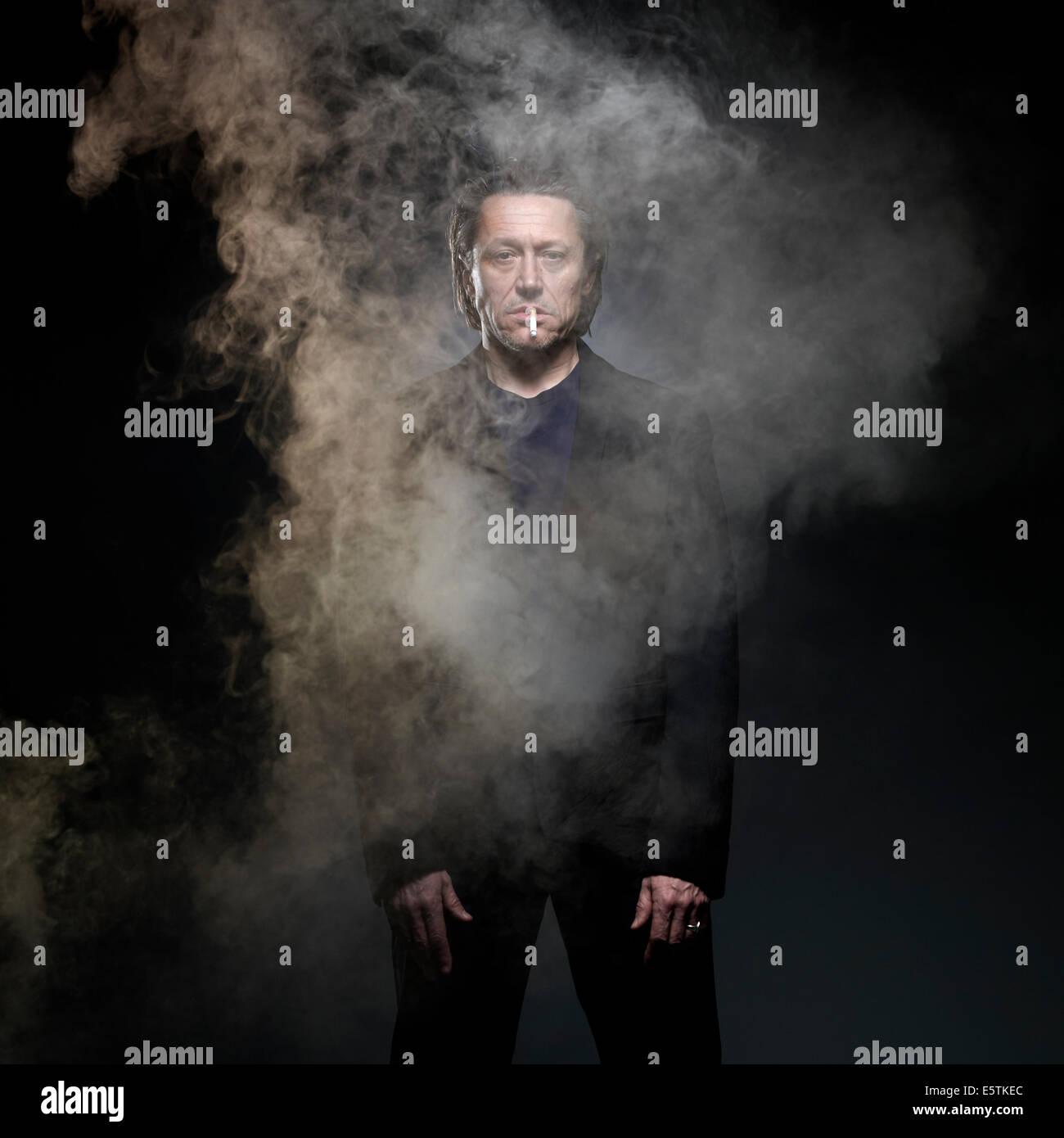 Robert Crampton who is a cigarette smoker studio shot wear black suit - Stock Image