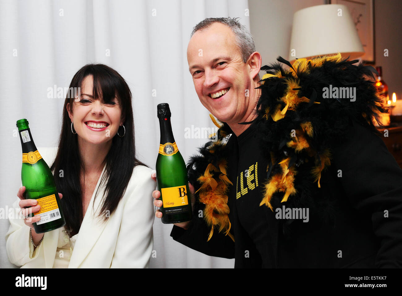 Party couple posing with Champaign bottles and smiling - Stock Image