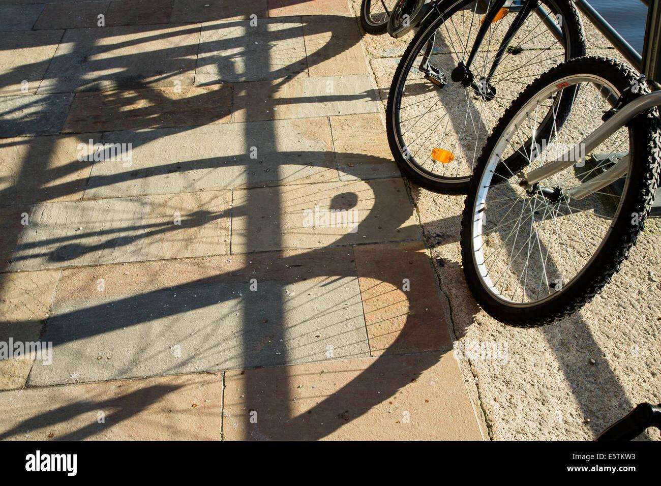 Bike shadows on pavement - Stock Image