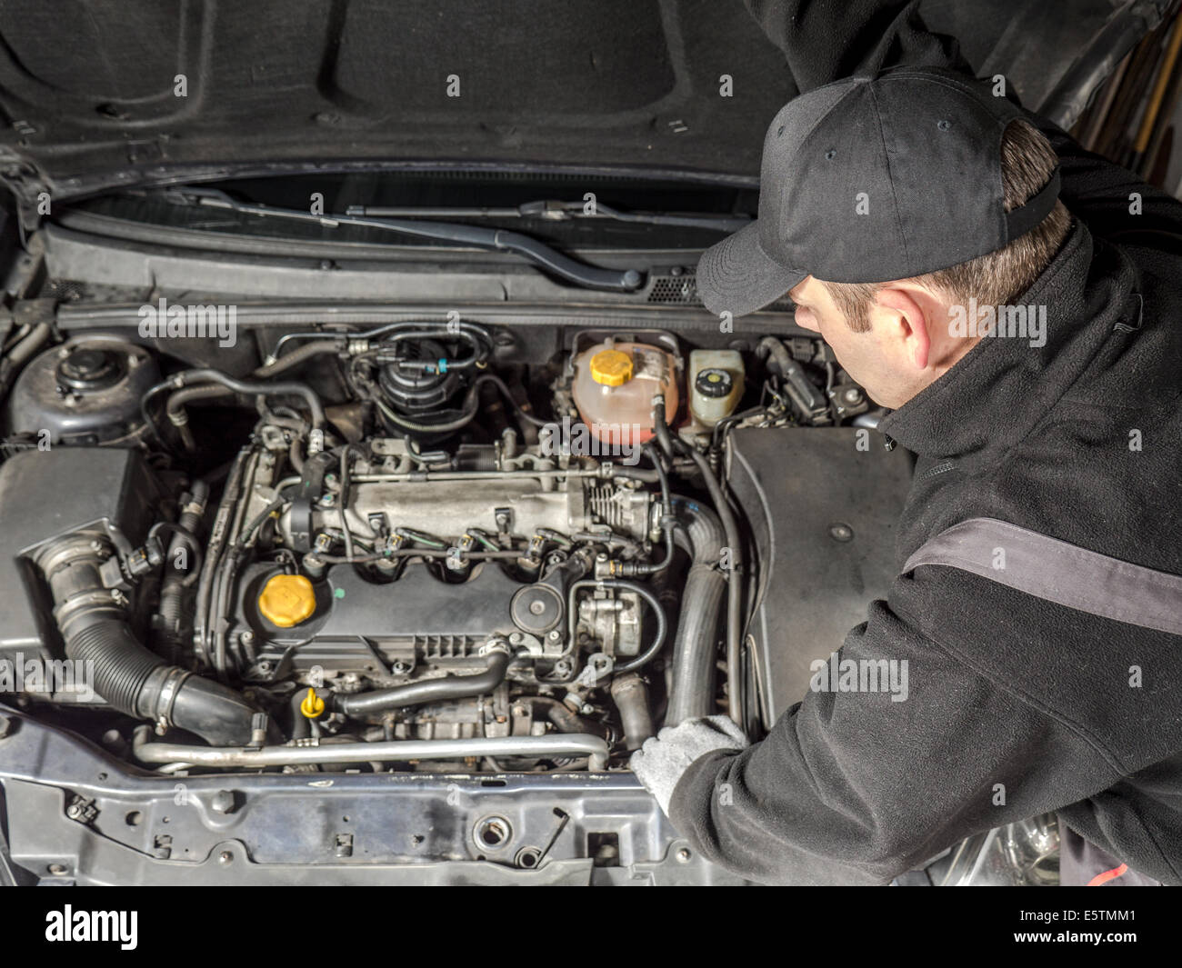 Auto mechanic inspecting car engine compartment - Stock Image