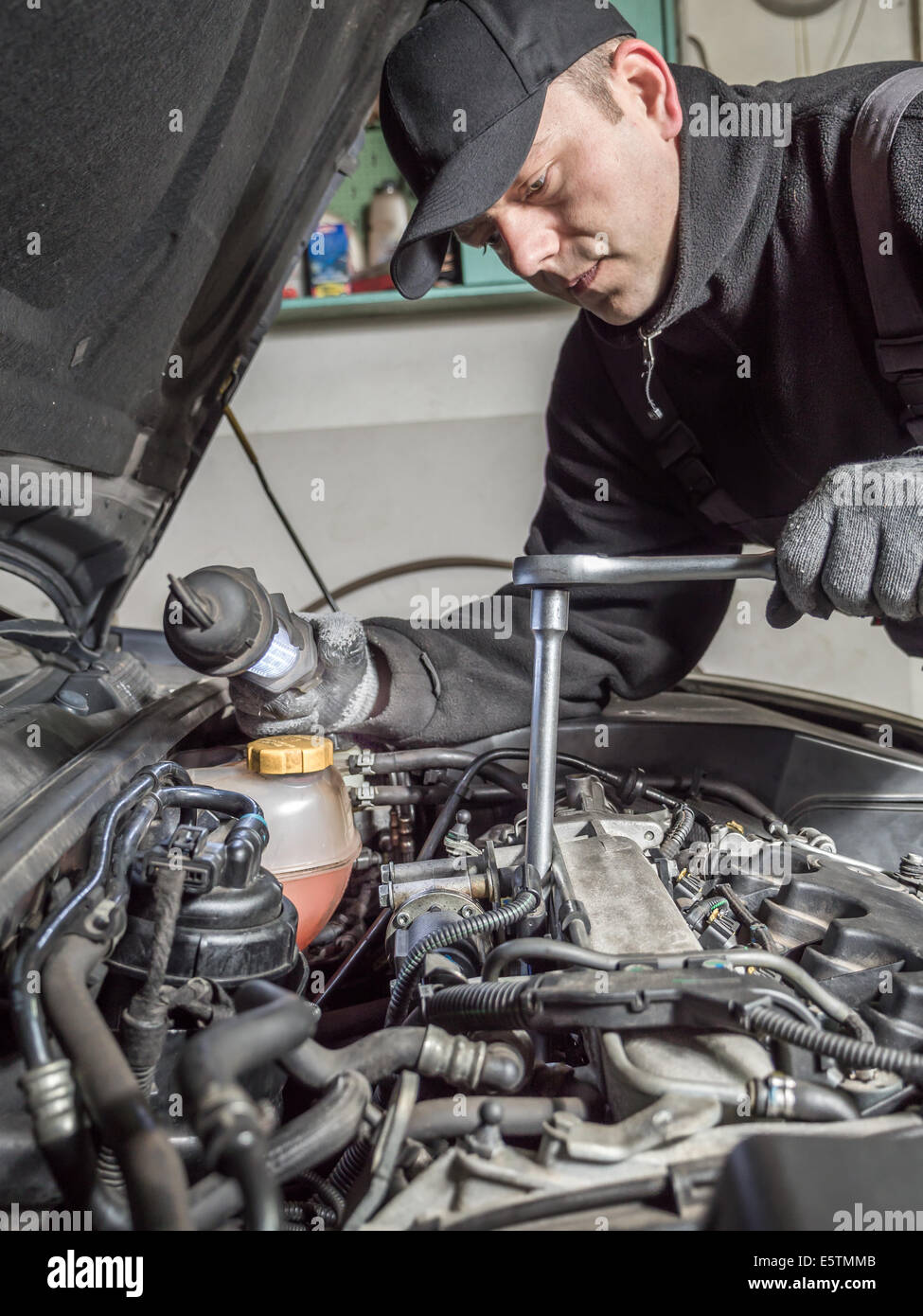 Auto mechanic replacing glow plugs in car diesel engine using spark plug spanner - Stock Image