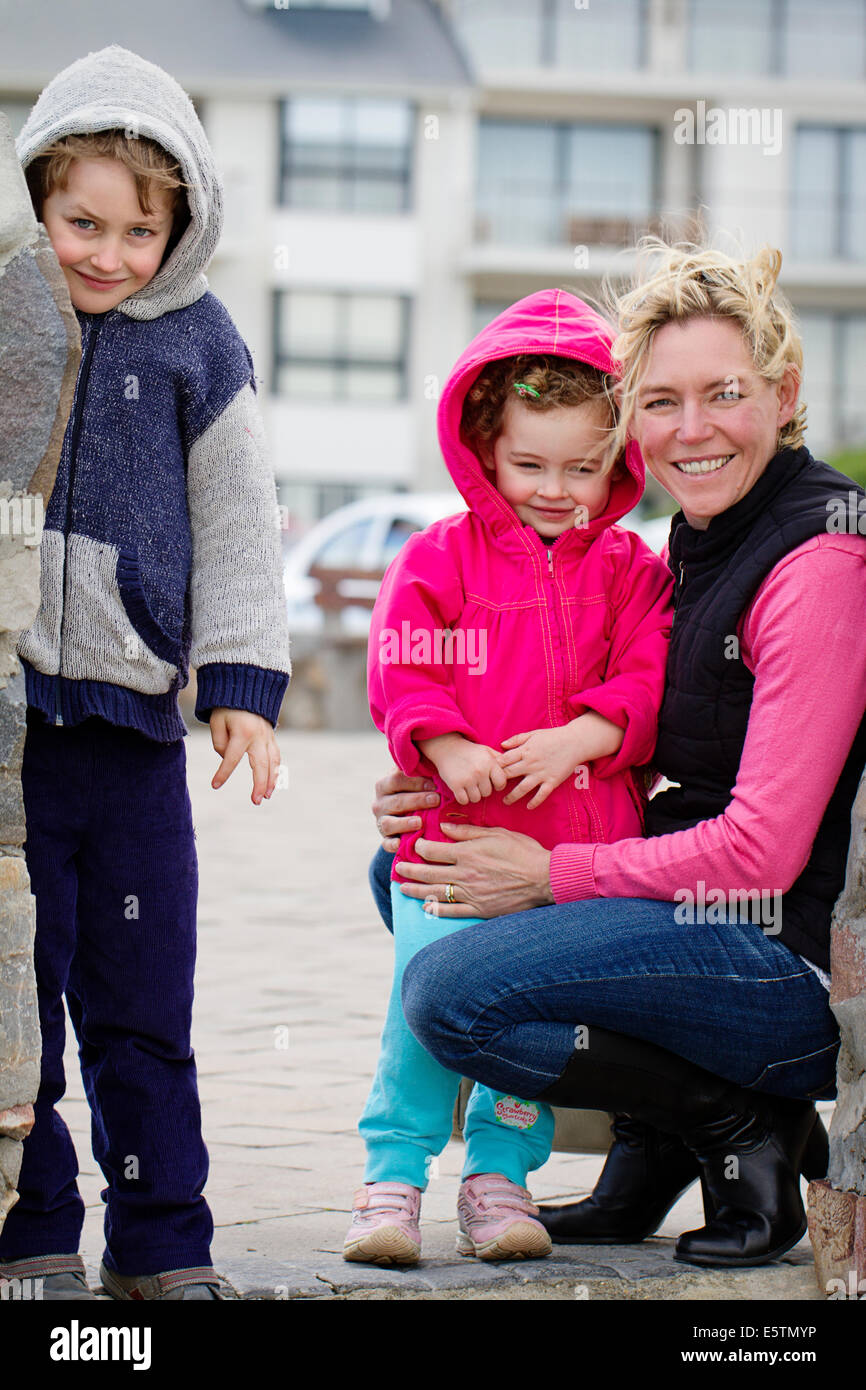 Warmly dressed young young boy and girl with their mom - Stock Image