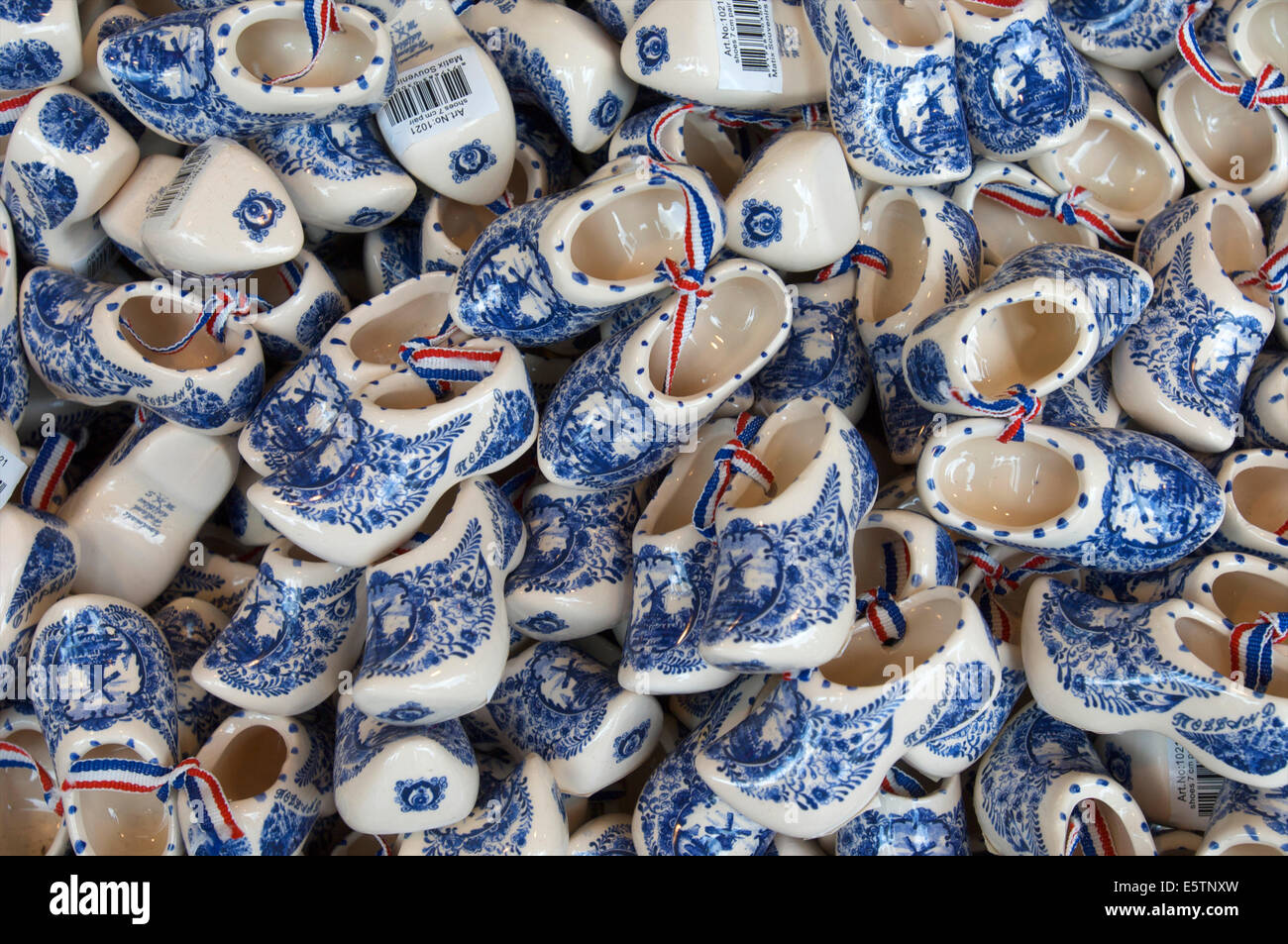 A basket with pottery Delft Blue wooden shoes as souvenirs in a shop in Volendam, The Netherlands - Stock Image