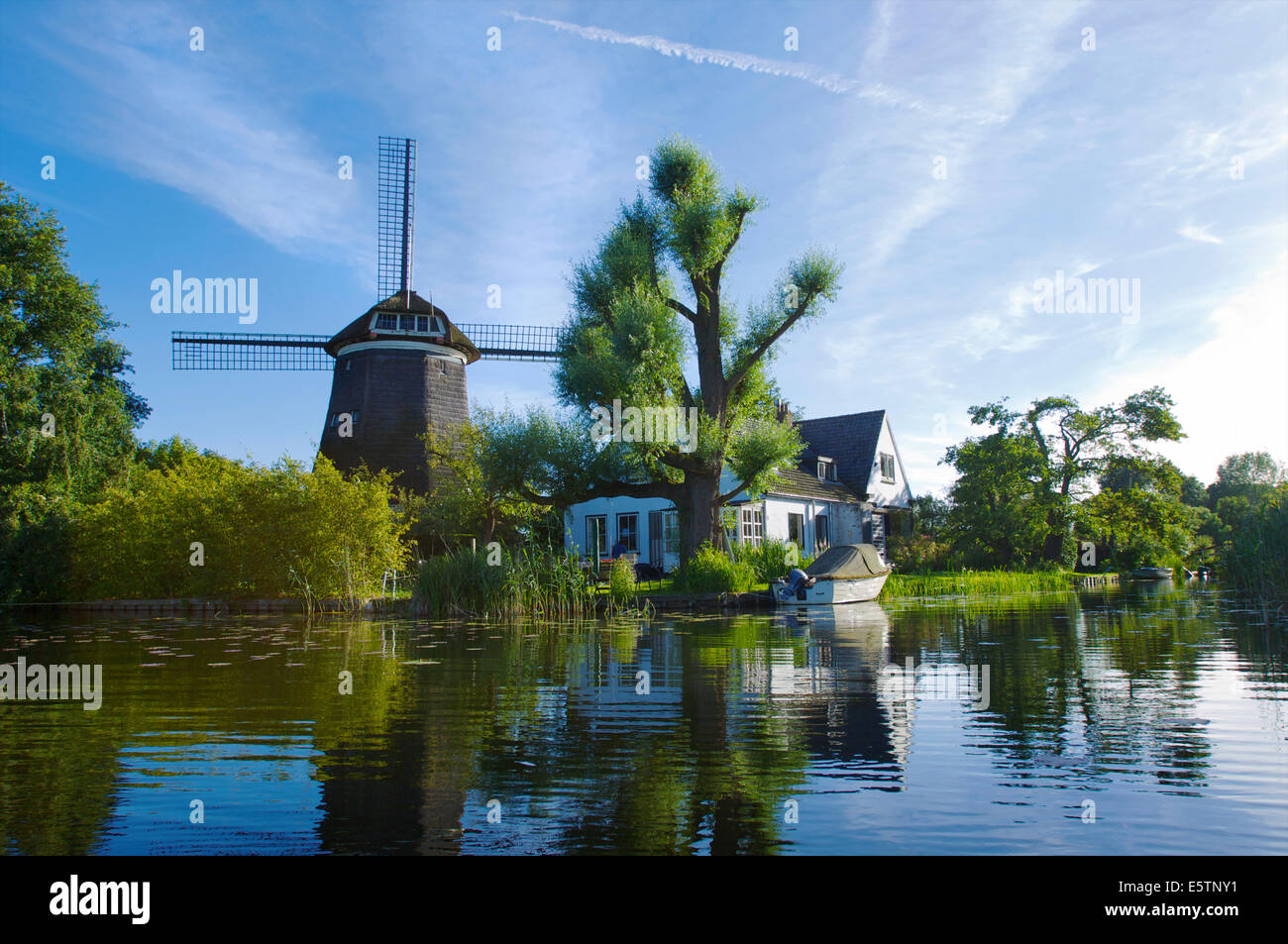 Beautifully located house with a windmill at the Spiegelplas or Mirror Lake in North Holland, The Netherlands - Stock Image
