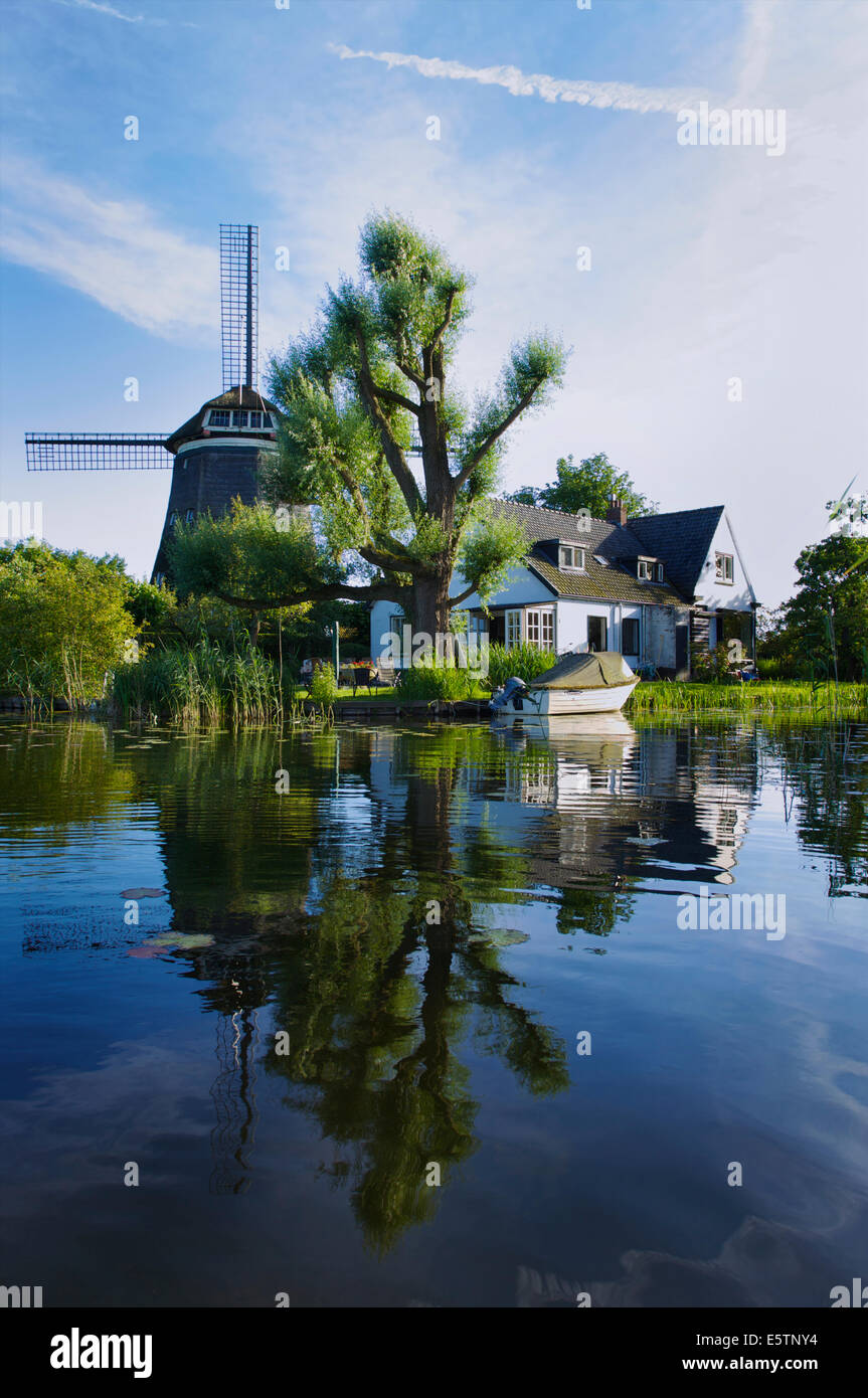 Lovely house with a windmill at the Spiegelplas or Mirror Lake in North Holland, The Netherlands - Stock Image