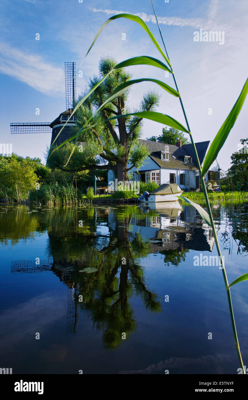 Picturesque house with a windmill at the Spiegelplas or Mirror Lake in North Holland, The Netherlands - Stock Image