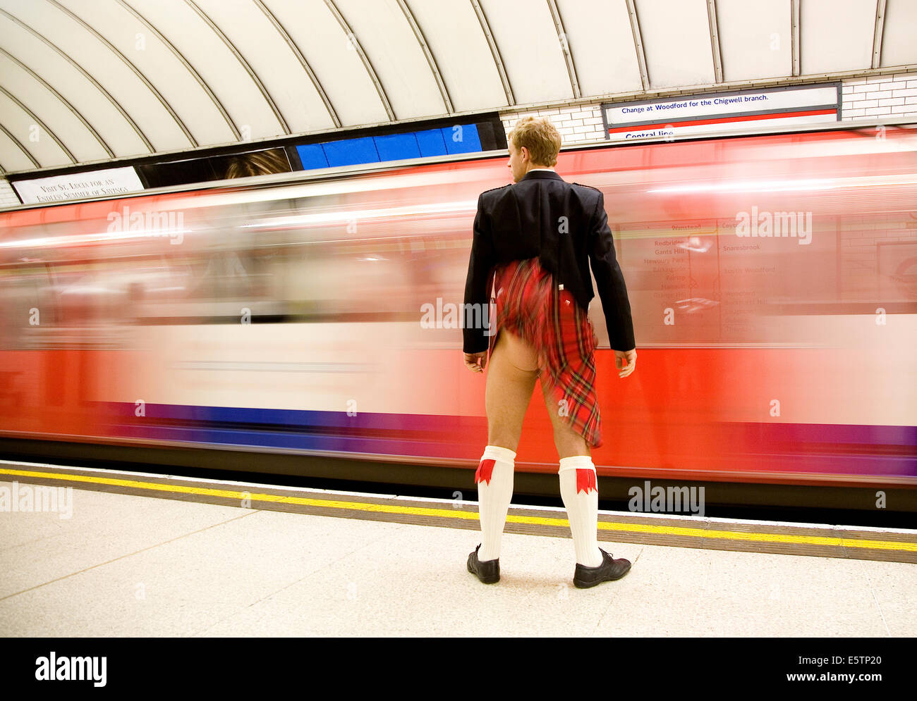 Kilt blows up in the wind as tube train comes into the station revealing a bare bottom - Stock Image