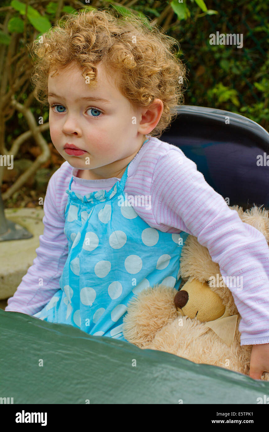Young curly haired girl and her teddy bear - Stock Image