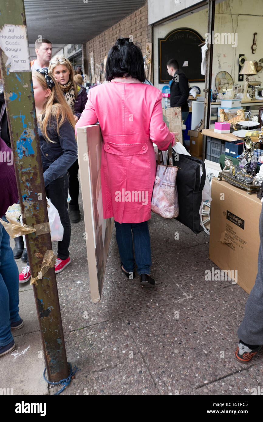 Woman in bright pink coat carrying painting at market - Stock Image