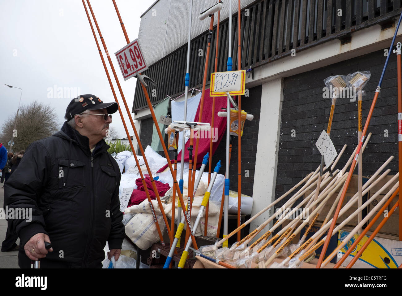 Man looking at Brooms Brushes and Mops For Sale - Stock Image