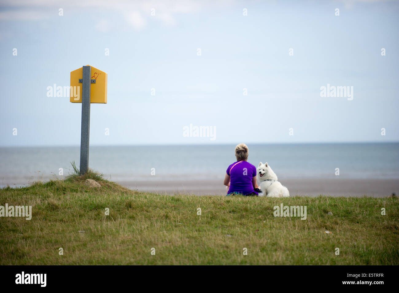 Port beach, County Louth, Ireland. 6th August, 2014. Karen Winters from Clogherhead, County Louth with her dog 'Lucky', - Stock Image