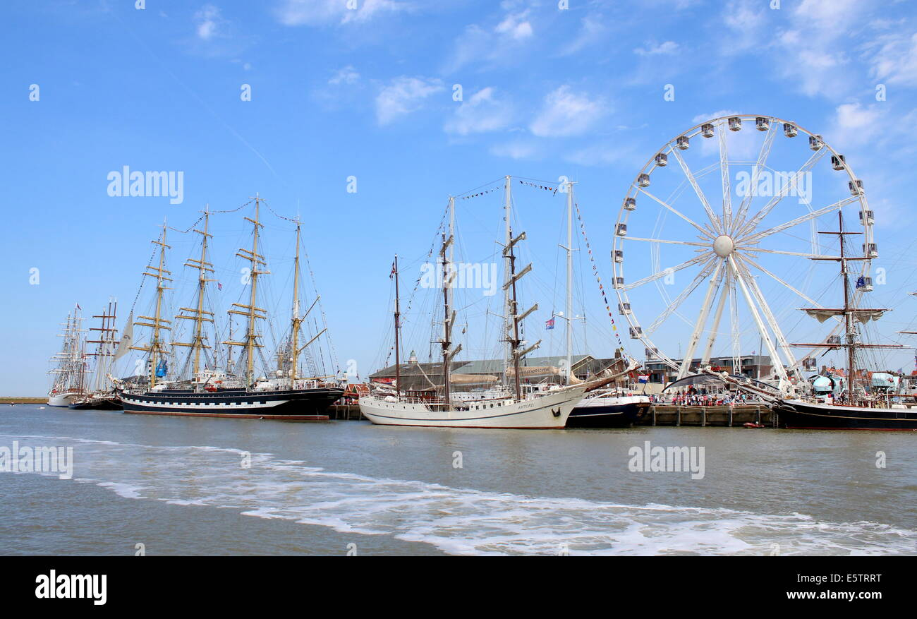 Tall ships Kruzenshtern and Artemis at the July 2014 Tall Ship Races in Harlingen, Netherlands, alongside a Ferris - Stock Image