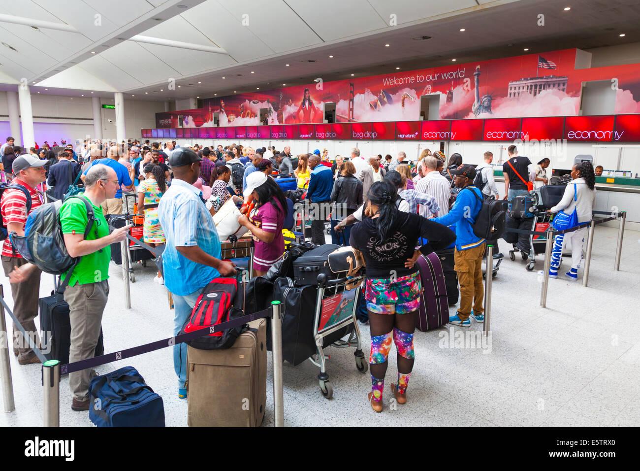 Long queue of passengers waiting to check in at Virgin Atlantic desks. - Stock Image