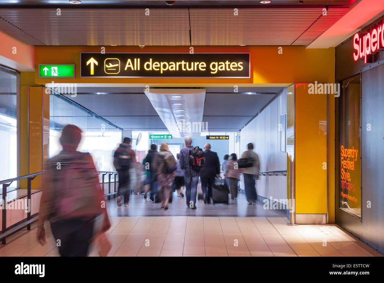 Passengers walking to Gatwick departure gates. - Stock Image