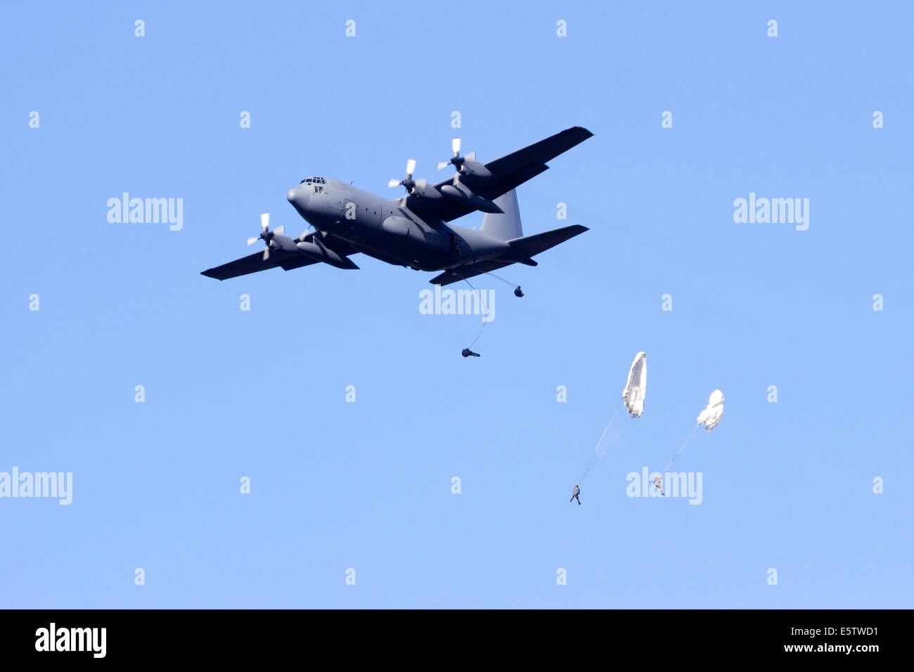 Military transport plane drops paratroopers Stock Photo