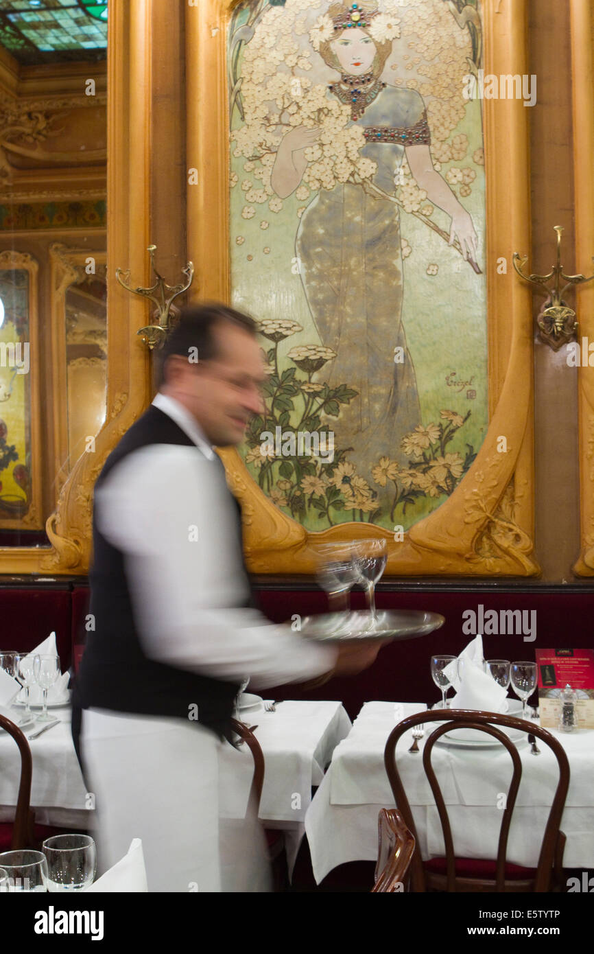 French waiter carrying a platter of wine glasses in Brasserie Julien Art Nouveau style in Paris. - Stock Image
