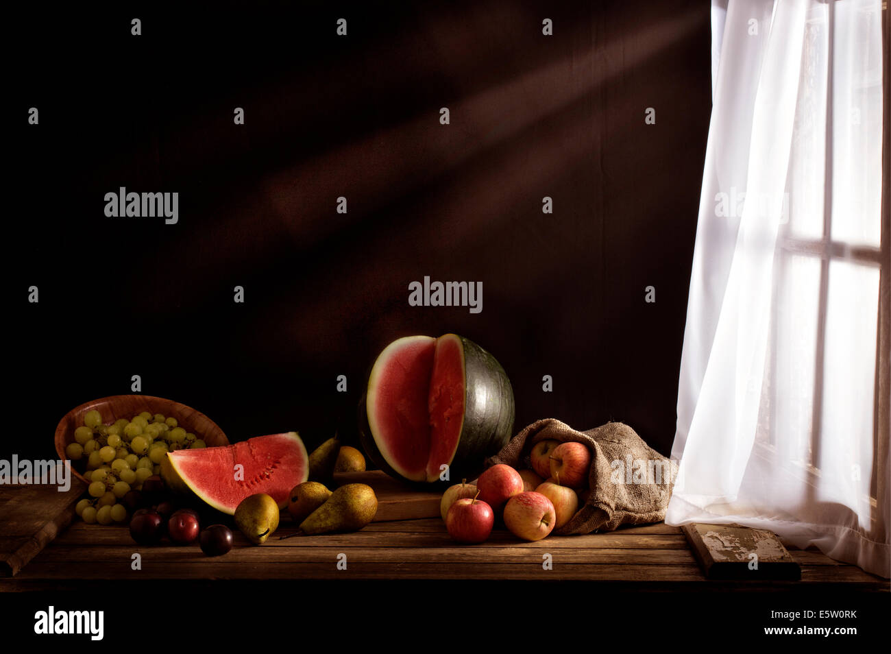 Moody still life of various fruits illuminated by a lace curtain window - Stock Image