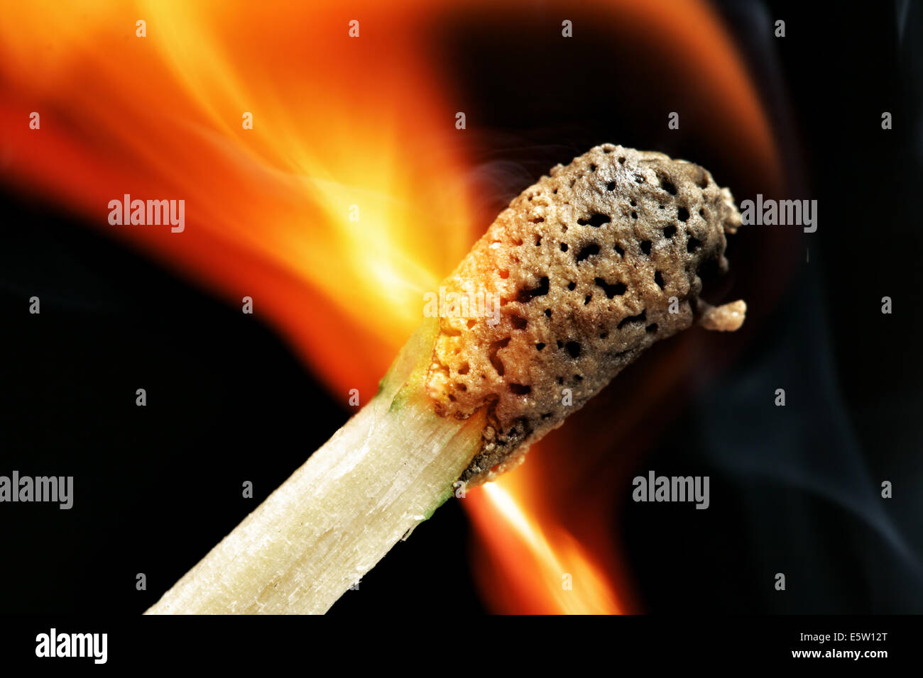 Burning match close-up over black background - Stock Image