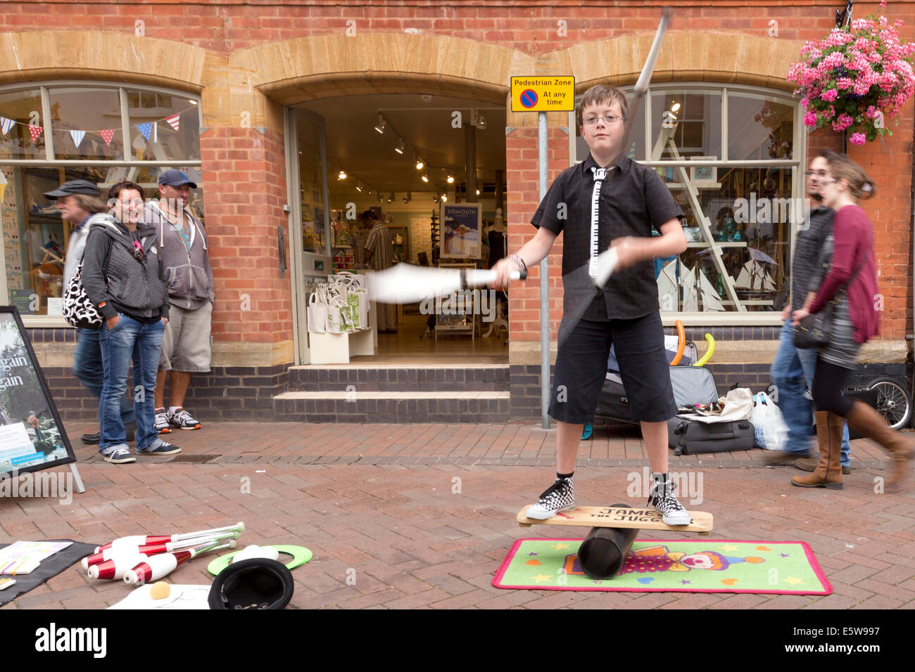 11 year old James the Juggler, juggling with knives whilst balancing on board on top of a pipe! Sidmouth 2014. - Stock Image