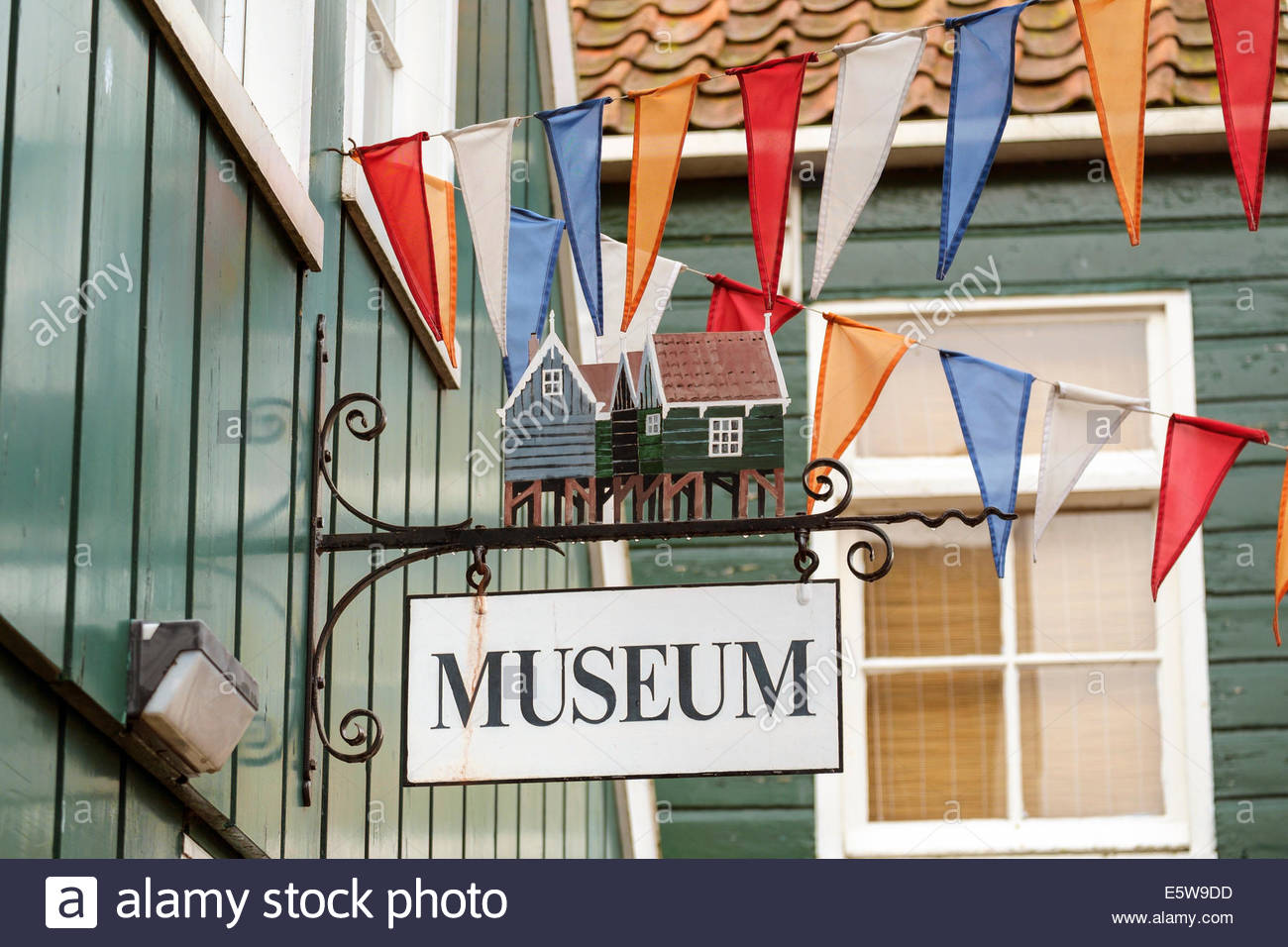 Museum sign and flags of Dutch national colors on building exterior, Marken, North Holland, Netherlands - Stock Image