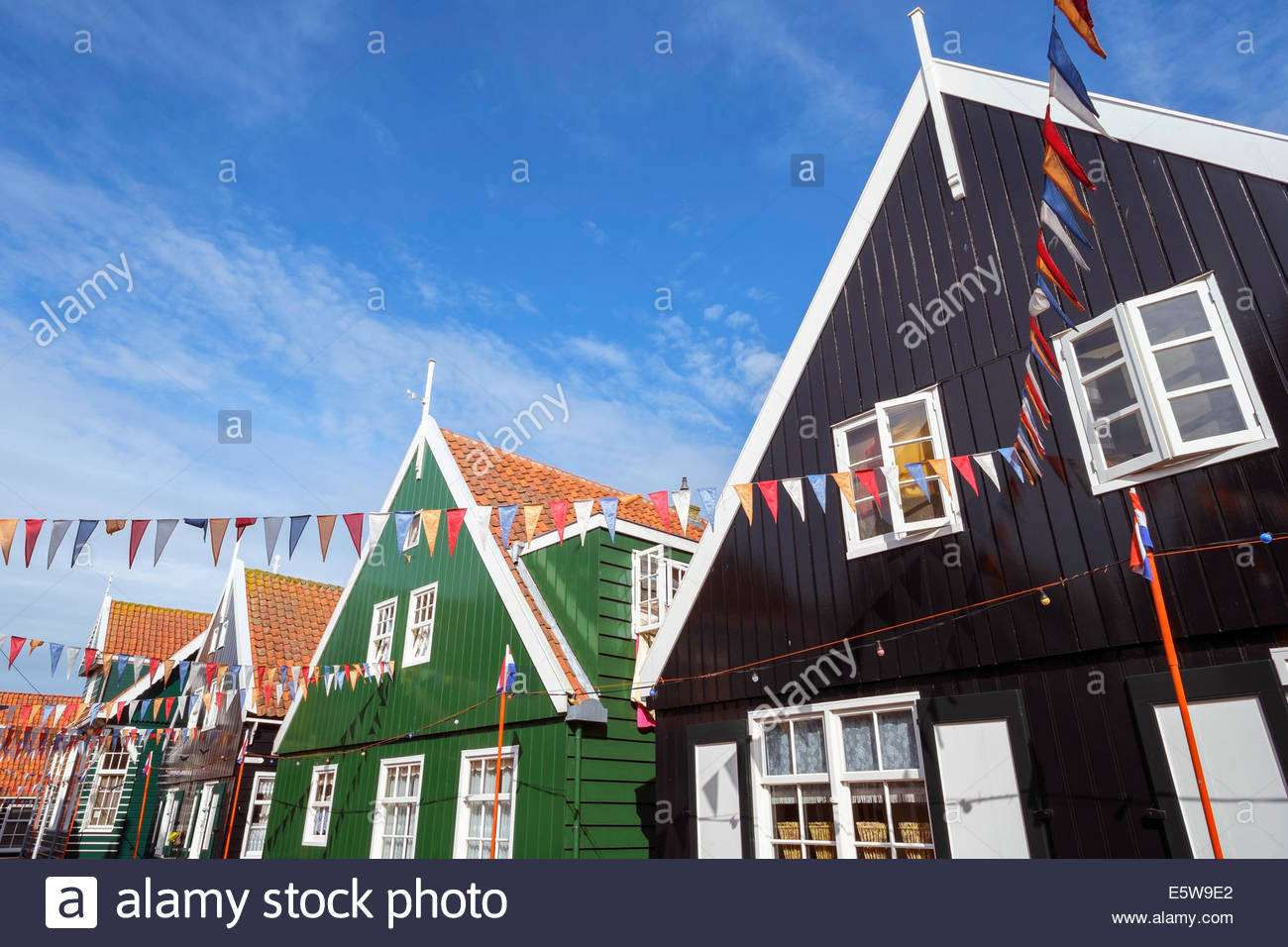 Traditional wooden houses decorated with flags of Dutch national colors for Koningsdag, or King's Day, Marken, - Stock Image