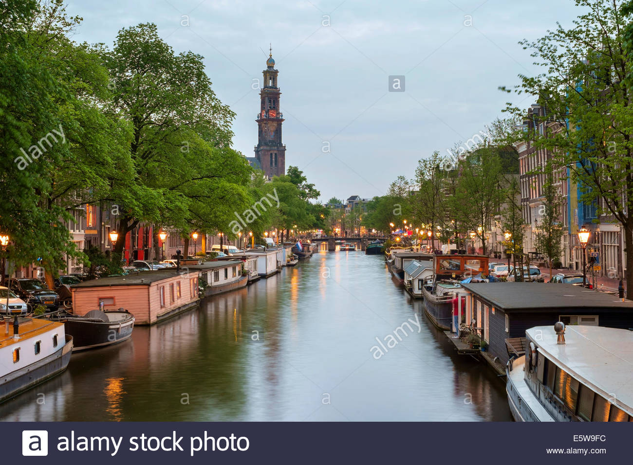 Prinsengracht canal at dusk with Westerkerk in distance, Amsterdam, North Holland, Netherlands - Stock Image