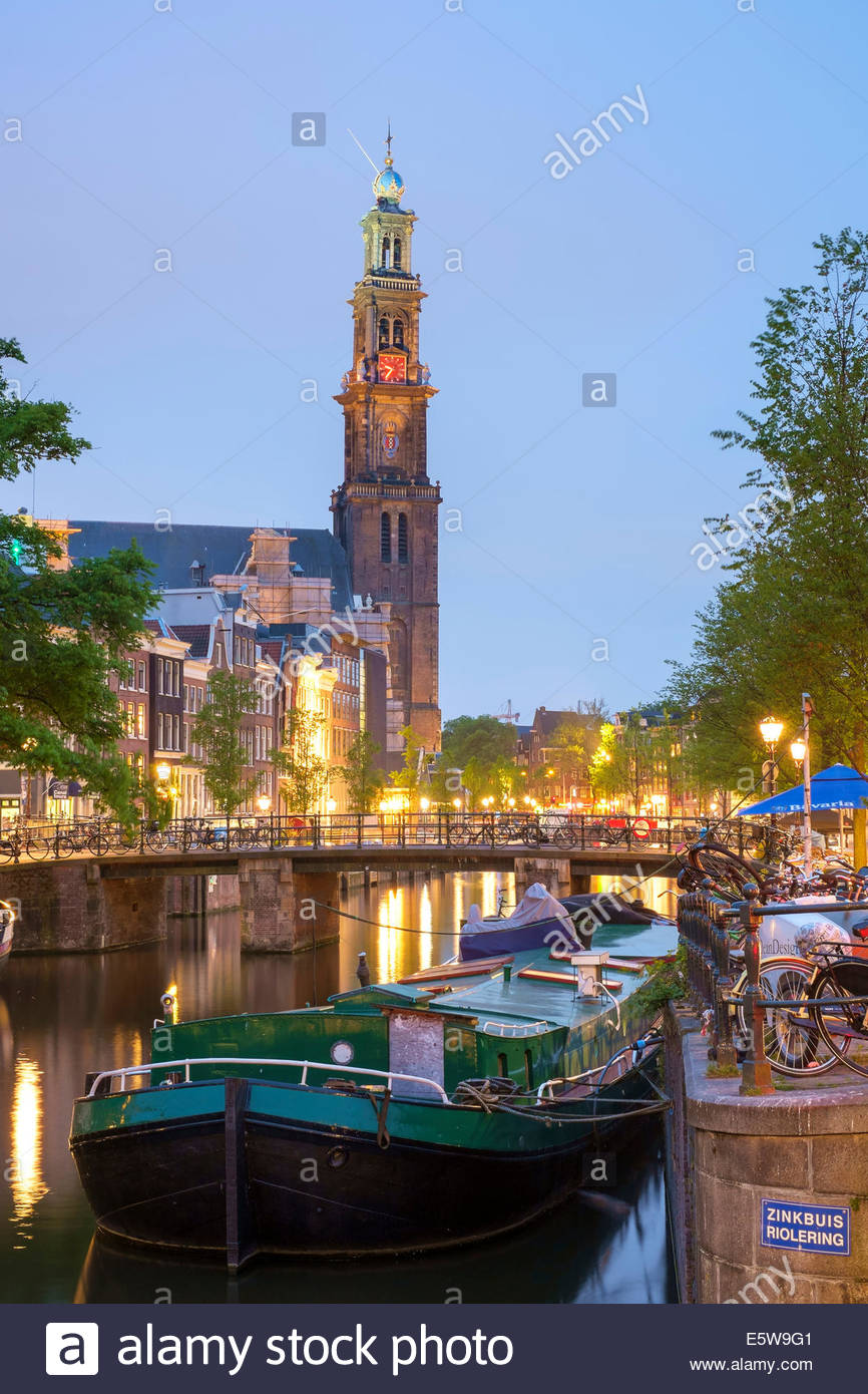 Prinsengracht canal and boat at dusk with tower of Westerkerk in distance, Amsterdam, North Holland, Netherlands - Stock Image