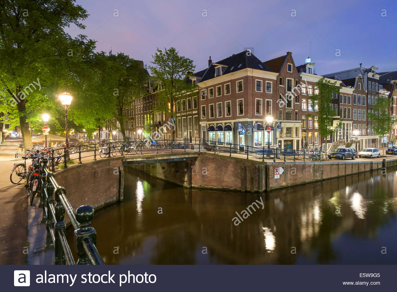 Intersection of Prinsengracht and Leidsegracht canals at night, Amsterdam, North Holland, Netherlands - Stock Image