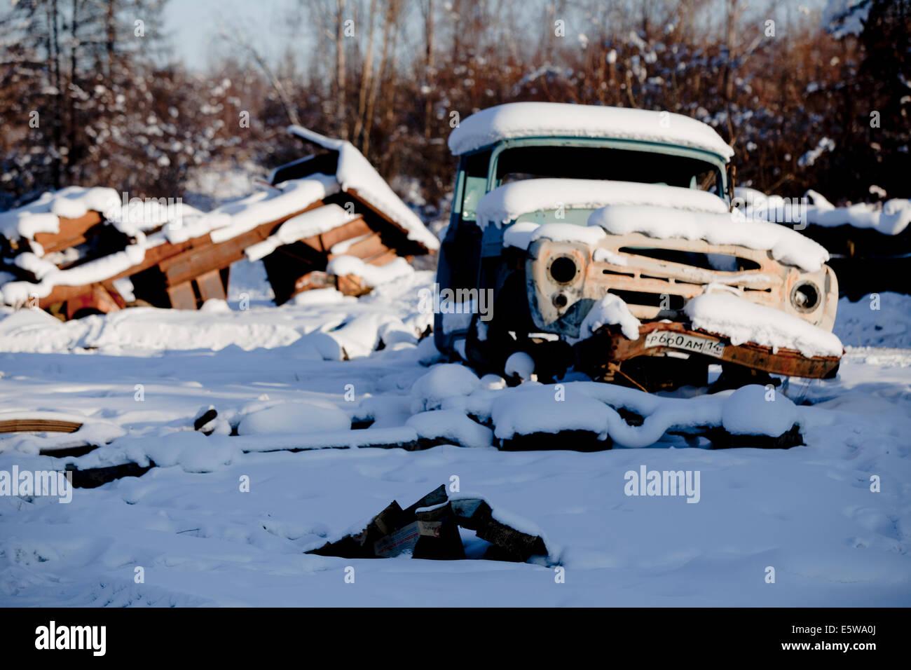 Abandoned snow abandoned car broken wall sun - Stock Image