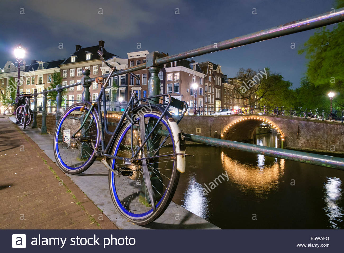 Bicycles along canal on the Herengracht at Reguliersgracht at night, Amsterdam, North Holland, Netherlands - Stock Image