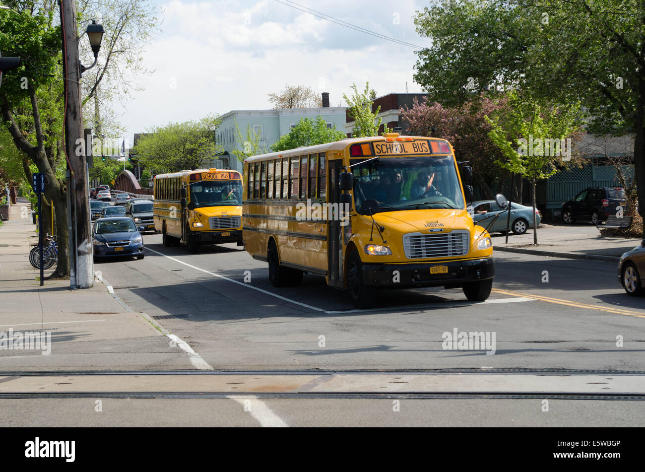 School buses stop at railroad intersection. - Stock Image