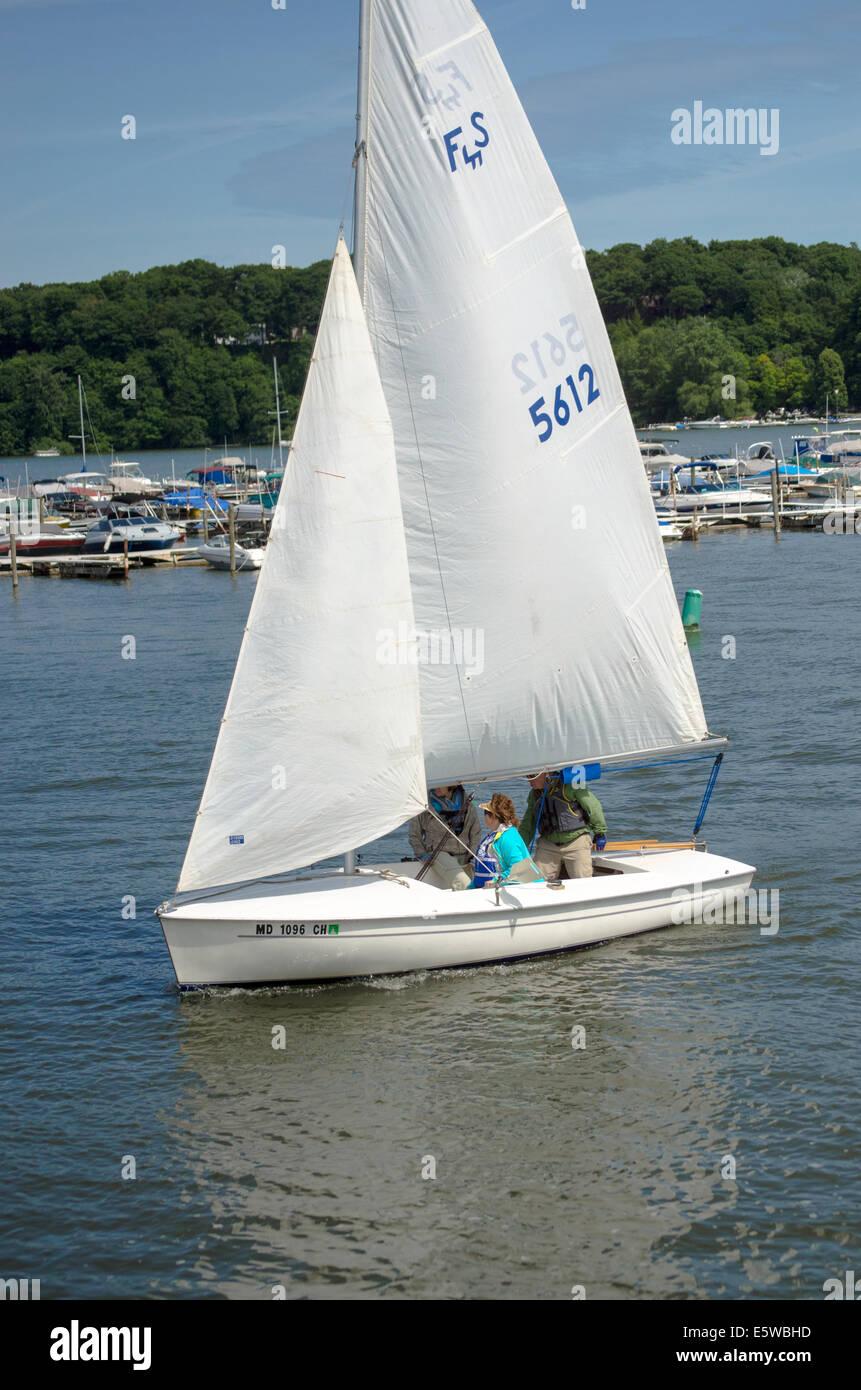 Sailer's set course in day sailer. - Stock Image