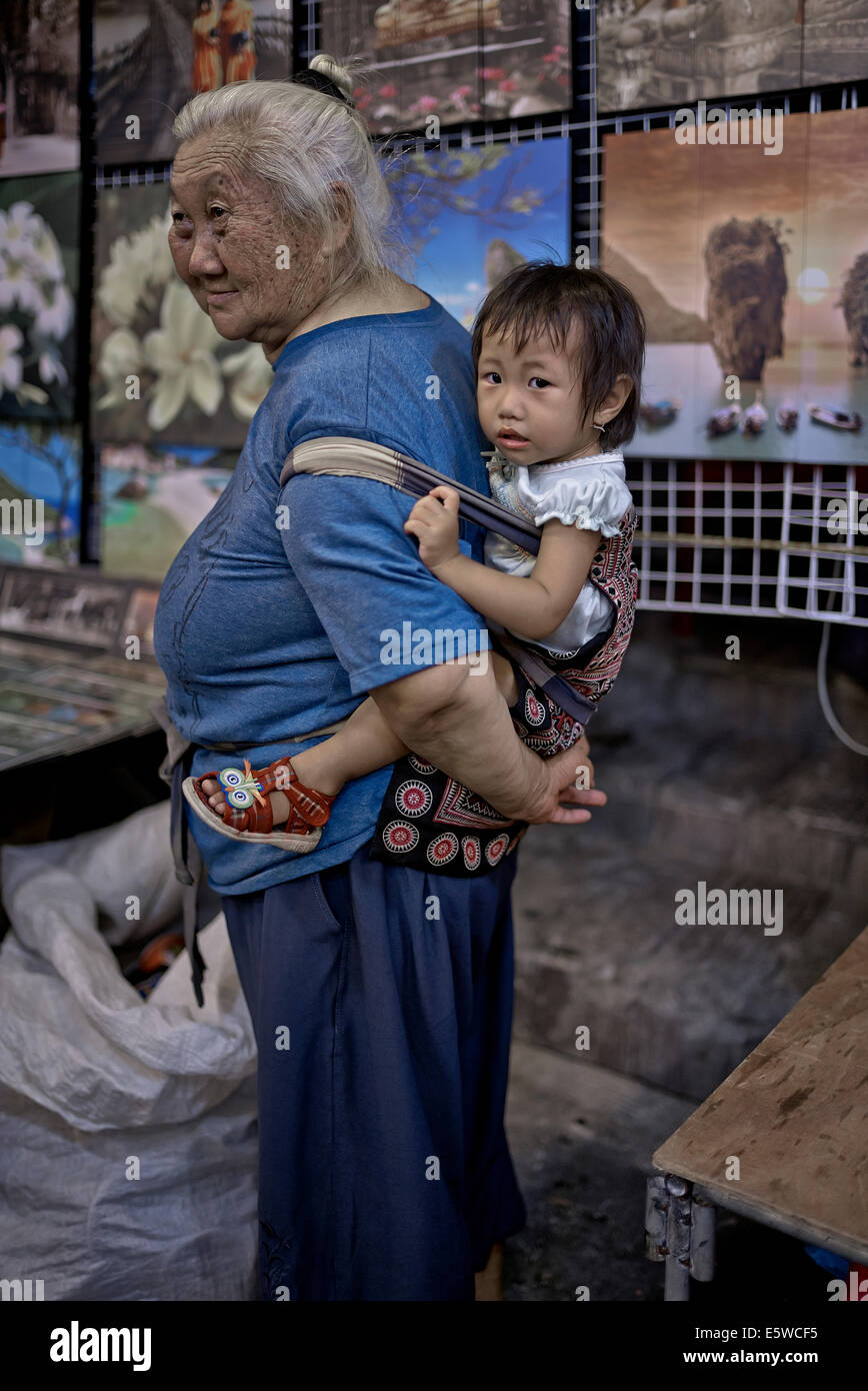 Thai grandmother carrying infant granddaughter in a back sling harness. Thailand S. E. Asia, Asian grandma carrying - Stock Image
