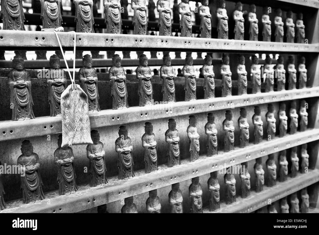 Rows of mini Buddha figurines line the inner sanctum of a Shinto Buddhist temple in Nagano City, Japan, Black and - Stock Image