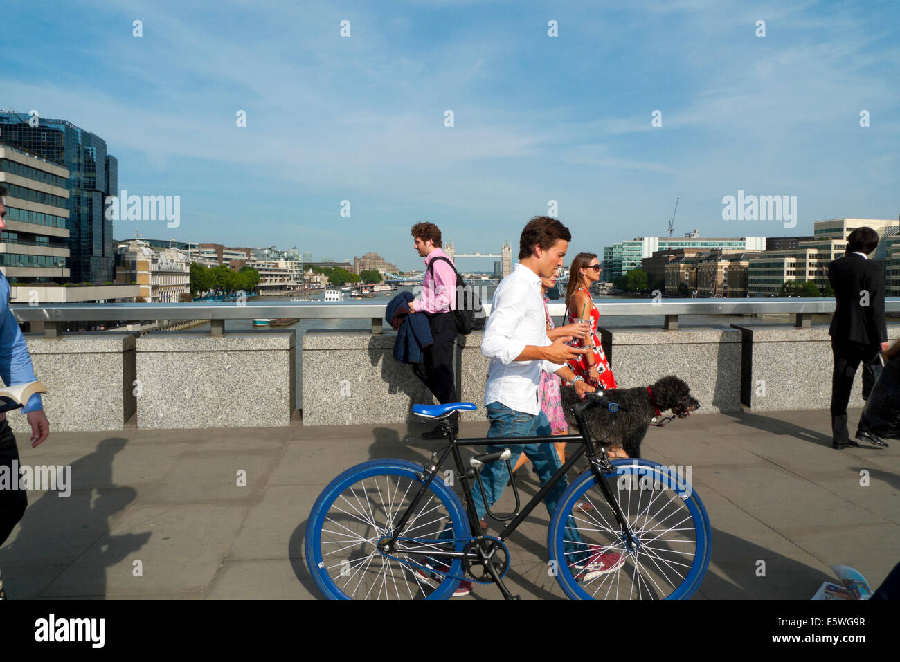 Man crossing London Bridge in summer sunshine  walking pushing a blue bicycle London UK   KATHY DEWITT Stock Photo