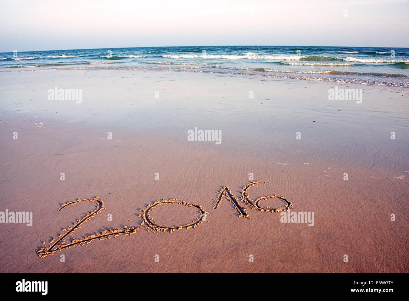 2016 written in sand, on tropical beach, in sunset - Stock Image
