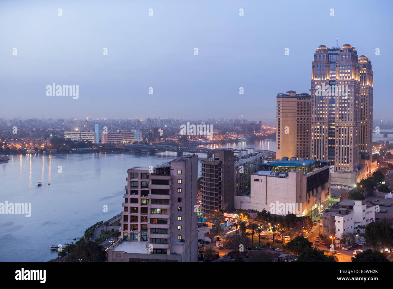 Nile River at dusk in Cairo, Egypt - with the Fairmont Nile City Hotel building on the waterfront - Stock Image
