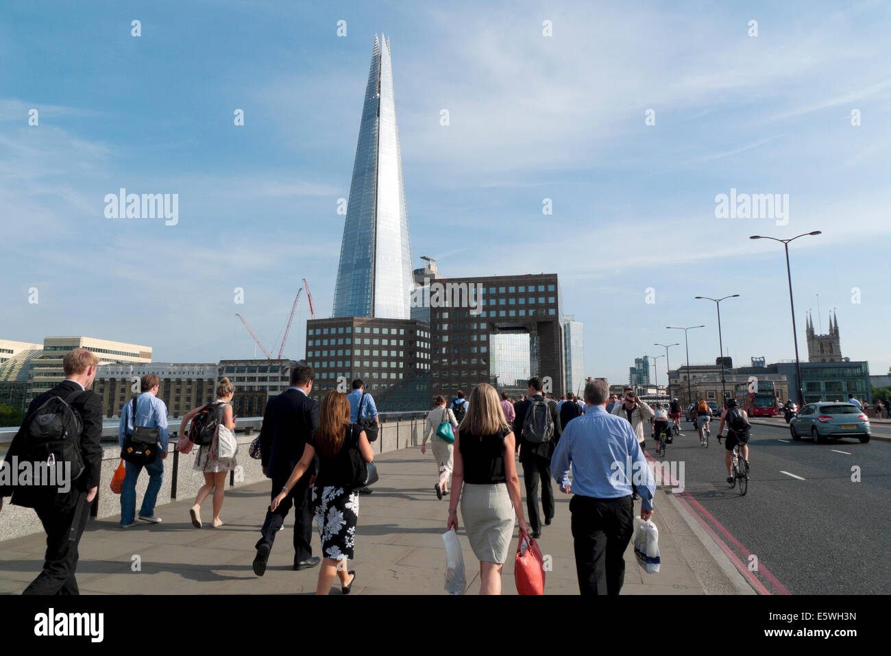 City of London office workers  crossing London Bridge at rush hour after work in summer with a view of the Shard - Stock Image