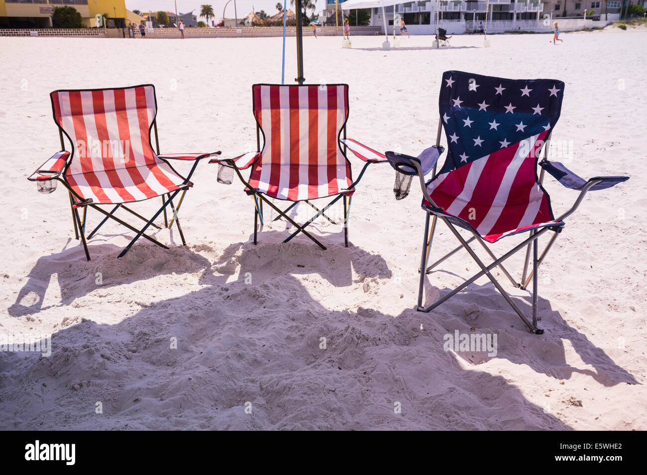 Three folding chairs on sandy beach in the design of US flag, USA - Stock Image