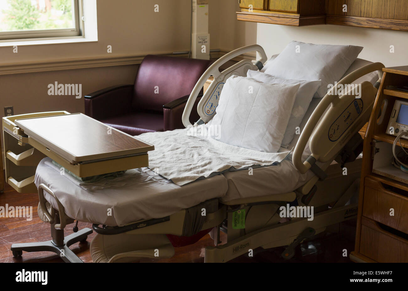 Empty hospital bed in USA maternity hospital with visitor