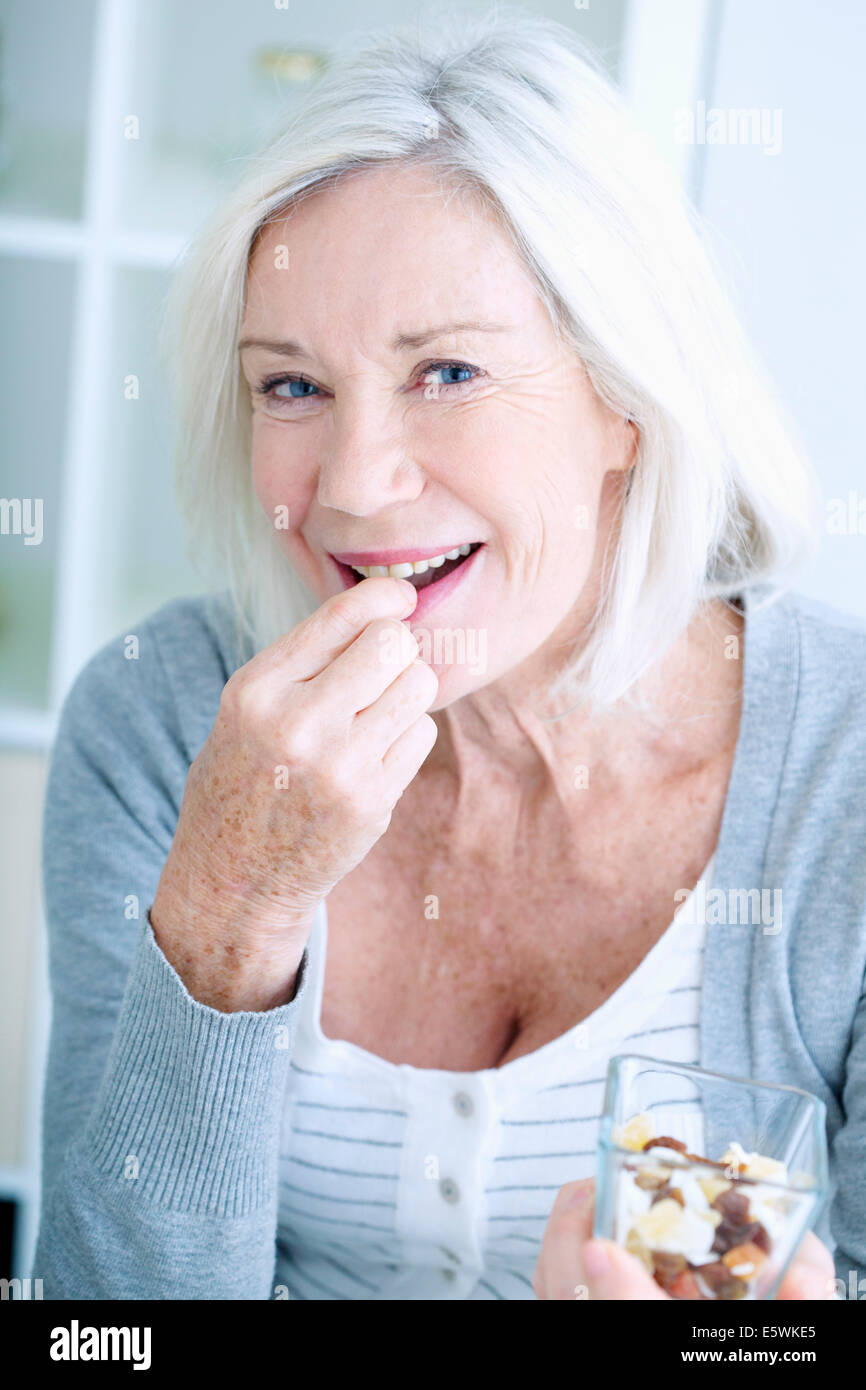 Elderly person eating dried fruit - Stock Image